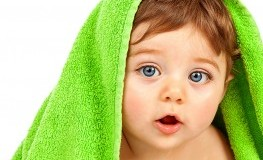 Image of cute baby boy covered with green towel isolated on white background, closeup portrait of ch